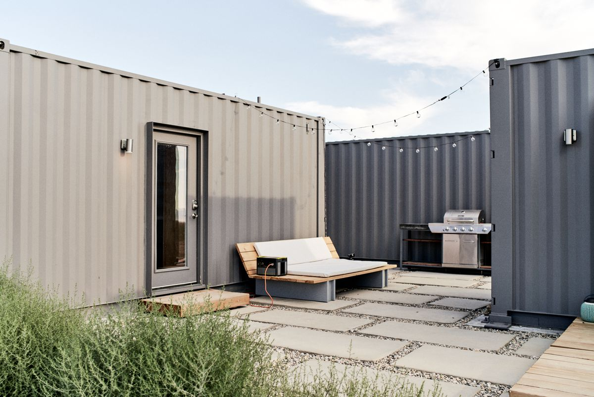 A concrete paver patio has string lights above and a large lounge couch in the center. Shipping containers on either side have been repurposed into a home.