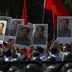 """Anti-Japan protesters hold portraits of the late Communist leader Mao Zedong, one of them marked with hand-written characters which reads """"People miss you,"""" while marching on a street outside the Japanese Embassy in Beijing, China, Tuesday, Sept. 18, 2012. The 81st anniversary of a Japanese invasion brought a fresh wave of anti-Japan demonstrations in China on Tuesday, with thousands of protesters venting anger over the colonial past and a current dispute involving contested islands in the East China Sea."""