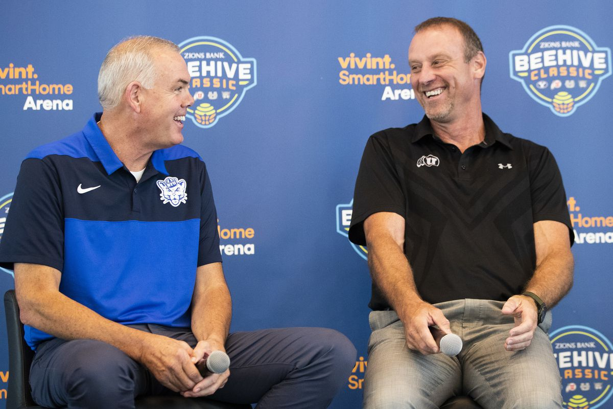 Head coaches Dave Rose, BYU, Larry Krystkowiak, Utah, share a laugh as they join other coaches Craig Smith, Utah State, and Randy Rahe, Weber State, to promote the Beehive Classic at a press conference at Vivint Smart Home Arena in Salt Lake City on Tuesd