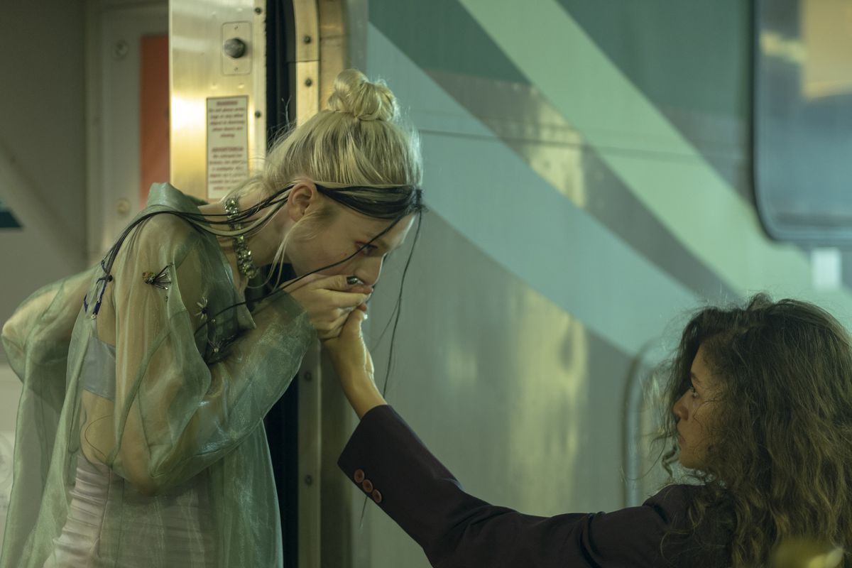 A girl with light blonde hair and a mesh cardigan stands at the open door of a train car, kissing the hand of another girl who stands below on the platform. They meet each others' eyes with a kind of longing, but it's clear that this is a goodbye.