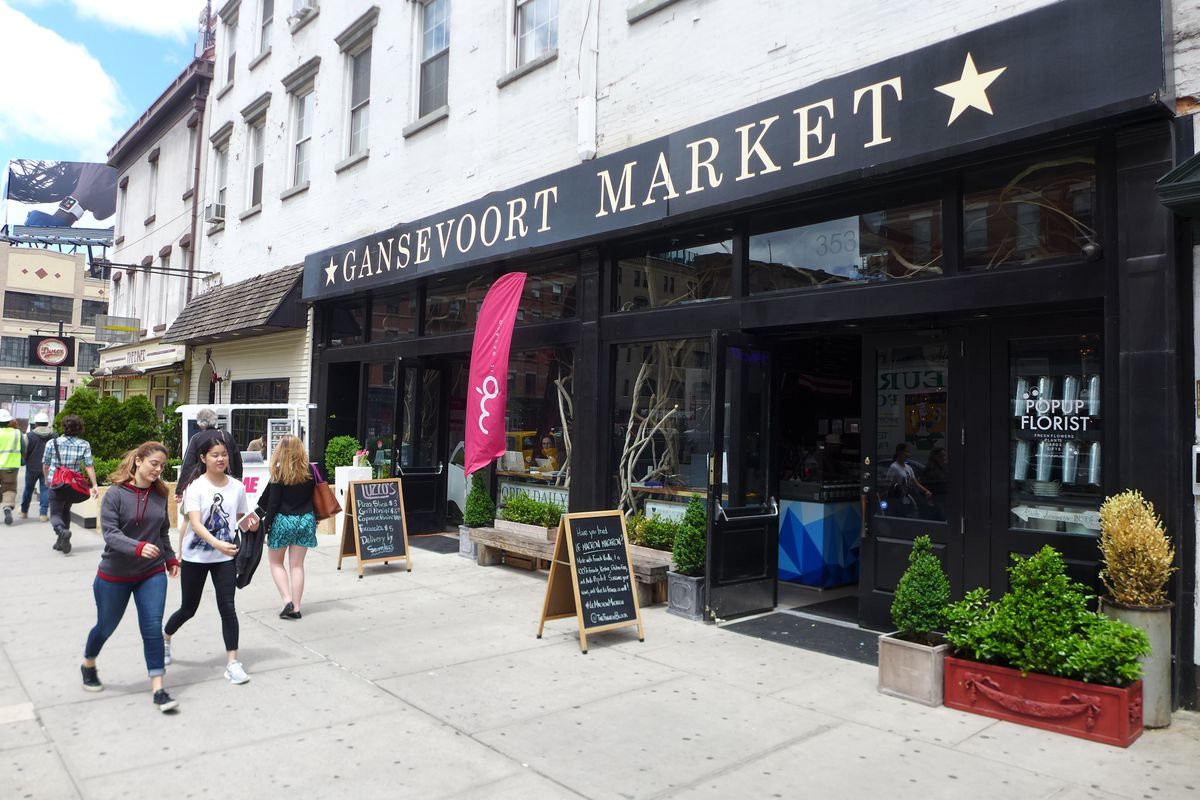 People walk in front of an open-air food hall, whose green awning reads Gansevoort Market