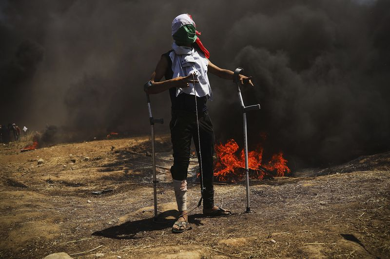A wounded Palestinian protestor stands at the border fence with Israel during mass demonstrations in Gaza City, Gaza.