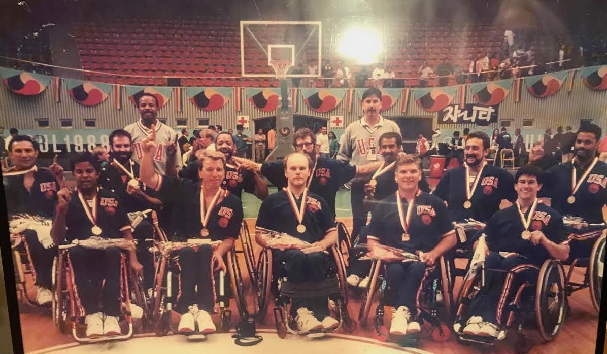"""The U.S. Men's Wheelchair Basketball Team won gold at the 1988 Paralympics in Seoul. Mustachioed head coach Frank Burns is seen standing, right. David Kiley is in the front row, signalling the team is """"No. 1."""""""