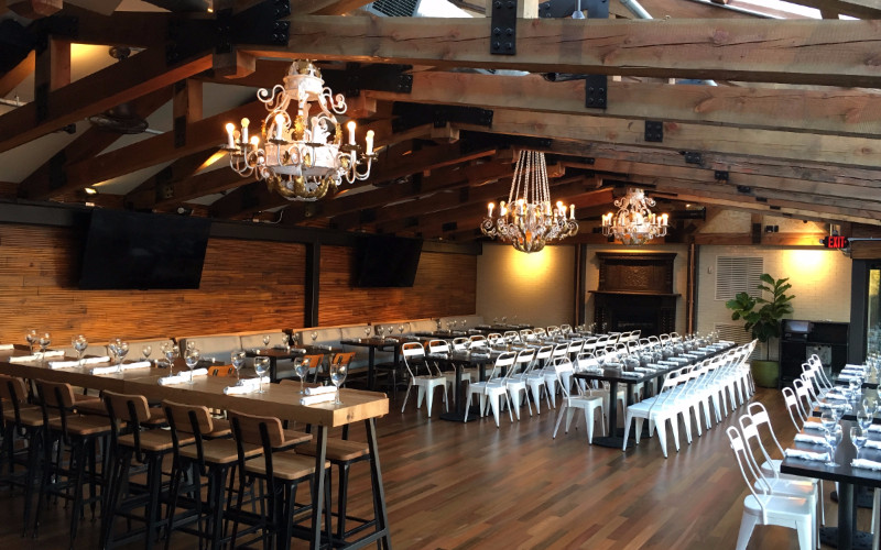 An open room with a chandelier, exposed beams, wood floors, and tables set with white chairs.