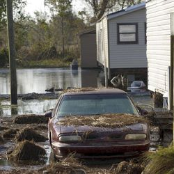 A car is covered in debris while other homes are surrounded by floodwaters in Ironton, La. after Hurricane Isaac near Louisiana Hwy 23 in Plaquemines Parish Monday, Sept. 3, 2012.