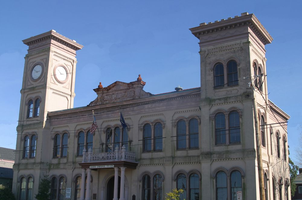 The exterior of the Algiers Courthouse in New Orleans. The facade is tan with multiple windows and two towers.