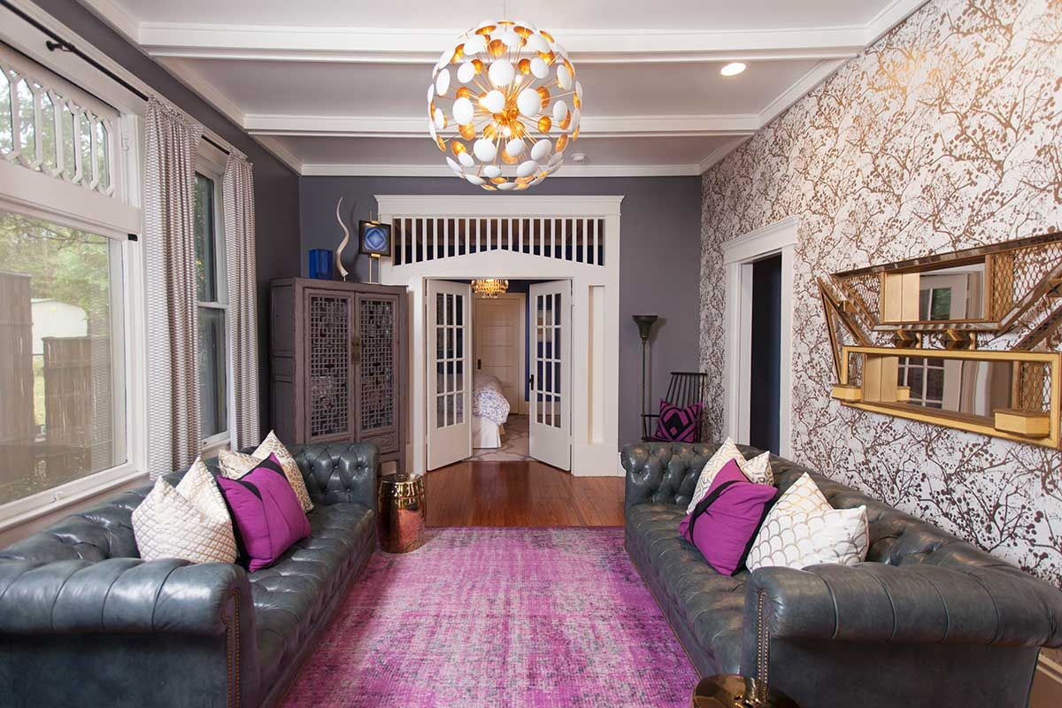 Living room with wallpaper, mod gold pendant fixture, gray chouches and wall with 1930s woodwork, purple accent pillows and purple rug
