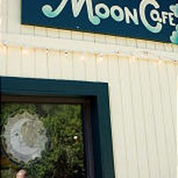 Carl Weyant is reflected in a window of his restaurant, The Sun \& Moon Cafe.
