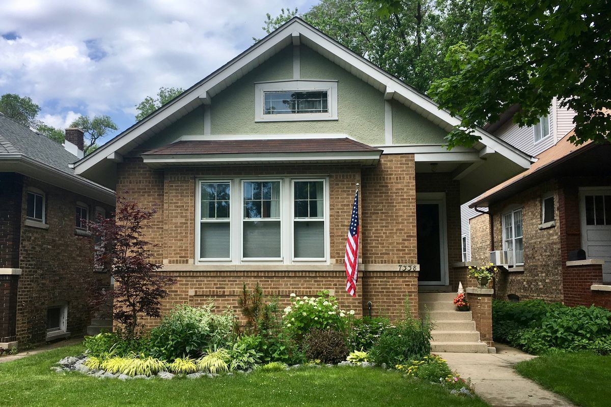 A bungalow with a brick exterior and bay window has an American flag near the door and an eclectic garden with a red-leaf tree, yellow and green shrubbery, and wildflowers.