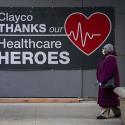 """The company Clayco hangs a sign on East Washington Street near North State Street in the Loop, thanking """"heathcare heroes"""" during the coronavirus pandemic, Monday morning, April 6, 2020."""