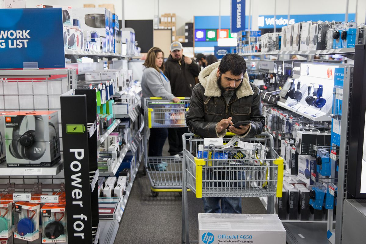 A shopper inside a Best Buy store leans on his shopping cart and looks at his phone.