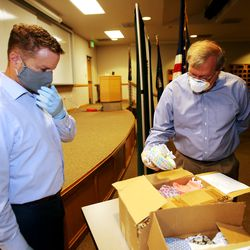 David Kelly, chairman the Pioneer Park Coalition, and Rick Graham, vice chairman of the coalition, examine a box of face masksat the Salt Lake County Sheriff's Office in South Salt Lake on Monday, May 11, 2020. The masks, which were made by members of Utah's Vietnamese community, will be given to inmates at the Salt Lake County Jail to help slow the spread of COVID-19.