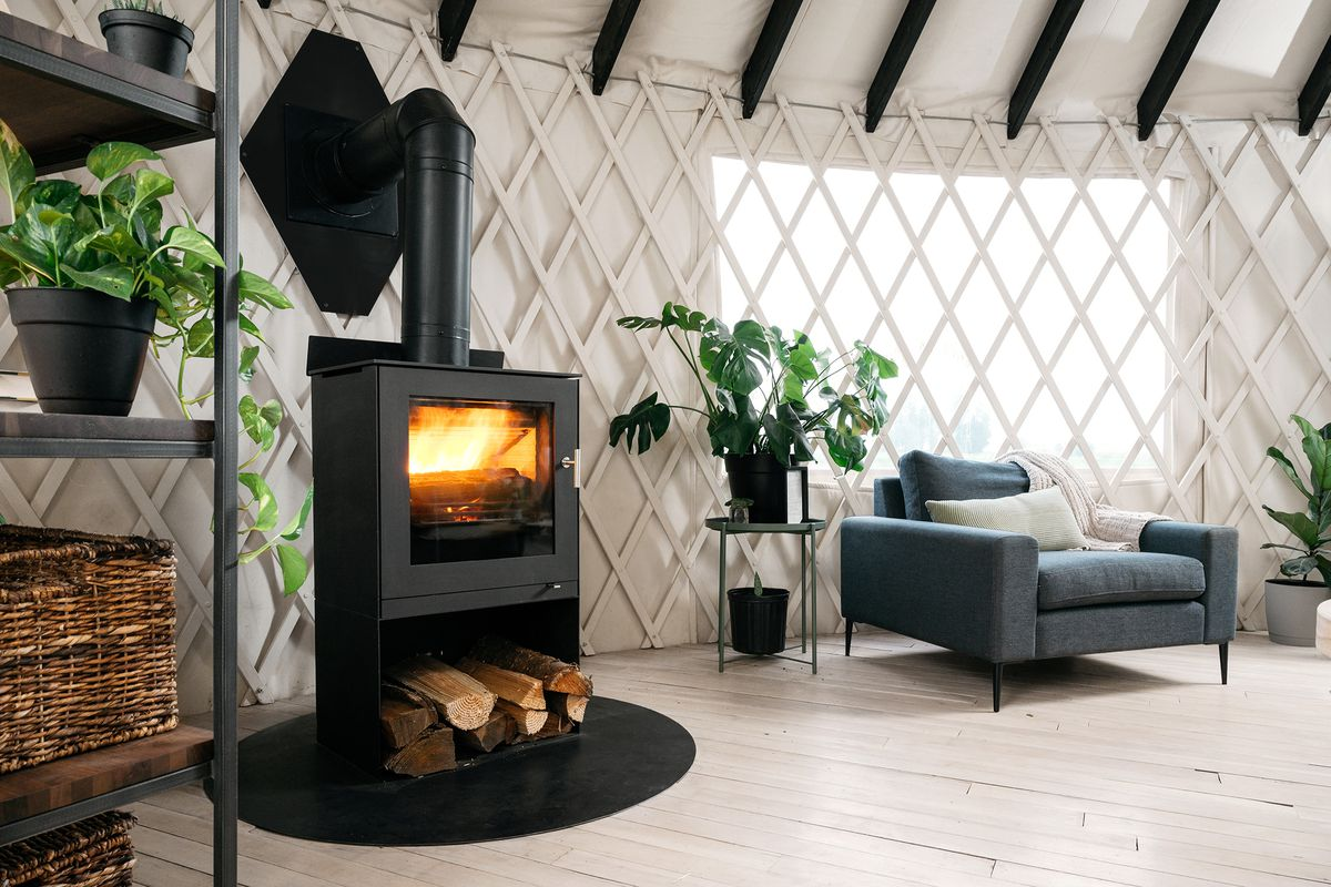 A black stove heats a white lattice yurt, with plants and a gray armchair in the picture.
