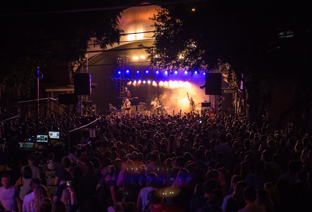 A packed crowd in front of a stage with lights and the band HAIM performing.