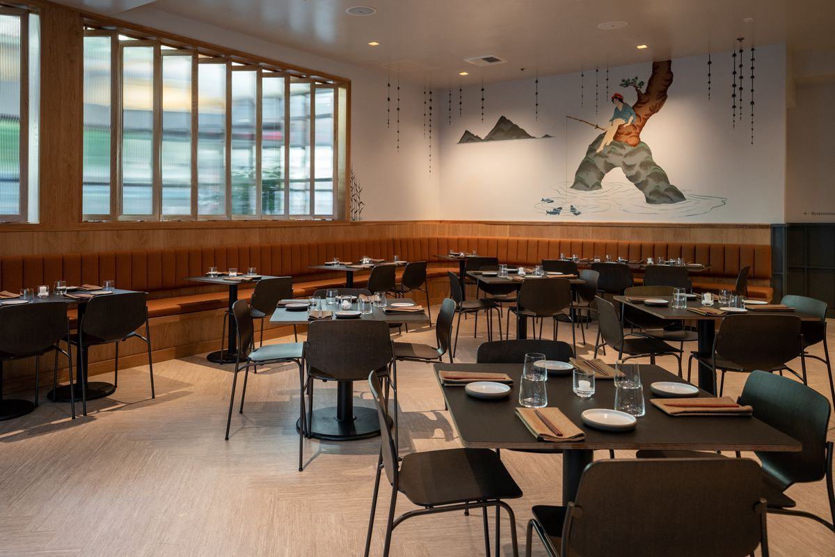 A view of Bamboo Sushi's dining room, with a mural on the back wall depicting Japanese pearl divers.