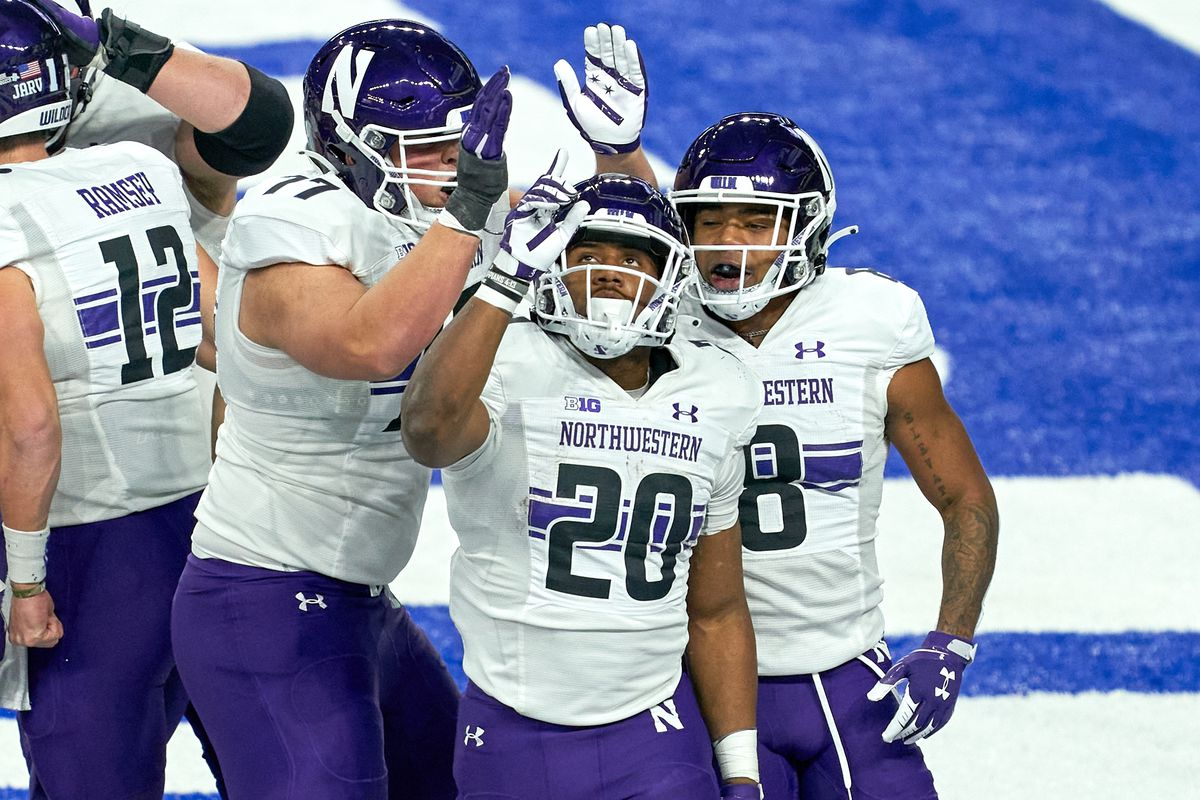 Northwestern Wildcats running back Cam Porter (20) celebrates with teammates after scoring a touchdown in action during the Big Ten Championship game between the Ohio State Buckeyes and the Northwestern Wildcats on December 19, 2020 at Lucas Oil stadium, in Indianapolis, IN.