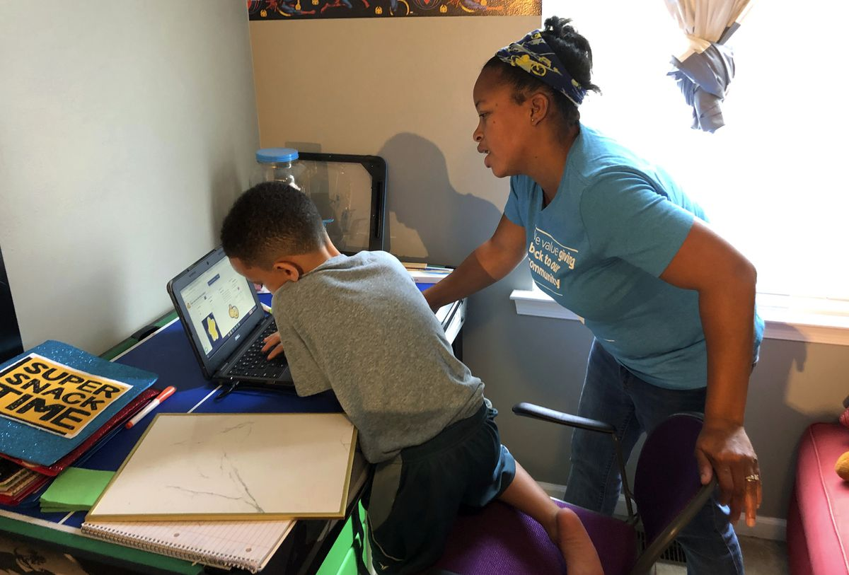 Tiffany Shelton helps her 7-year-old son, P.J. Shelton, a second-grader, during an online class at their home in Norristown, Pa