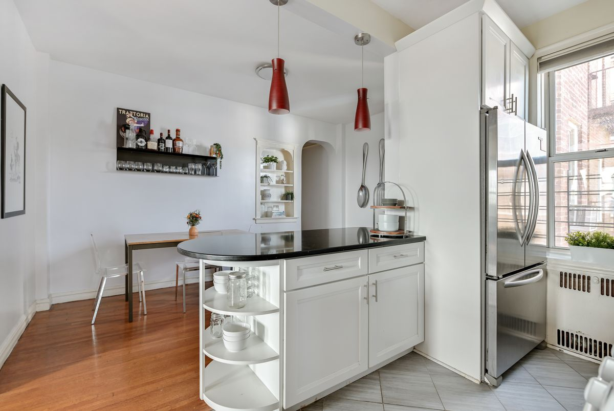 A kitchen with a small island and white cabinetry.