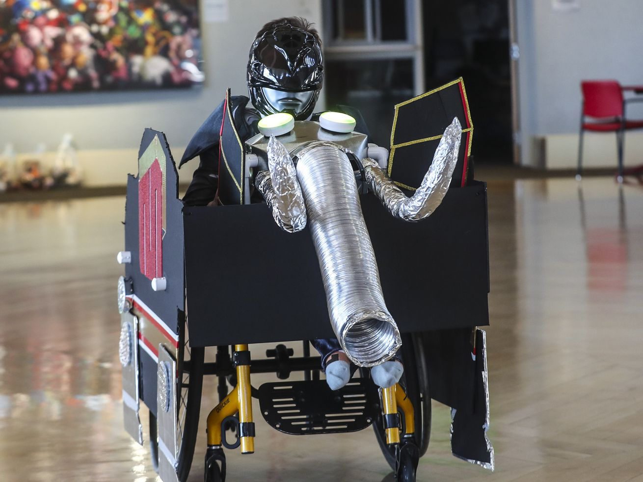 Skylar Skuza zips around in his Power Ranger costume and his decorated wheelchair at Shriners Hospitals for Children in Salt Lake City on Thursday, Oct. 15, 2020. Hospital staff and volunteers transformed his wheelchair during the hospital's annual wheelchair costume clinic.