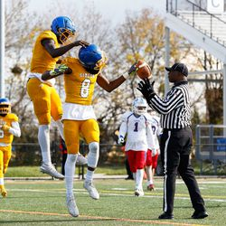 Simeon's George Gumbs (8) returns the ball and celebrates with Jacquez Woodland (1) after scoring a touchdown against Lakes.