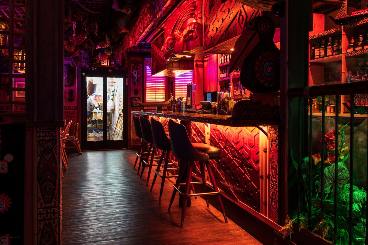 A red-lit bar with embossed details and high bar chairs. The bar glows in a dark space.