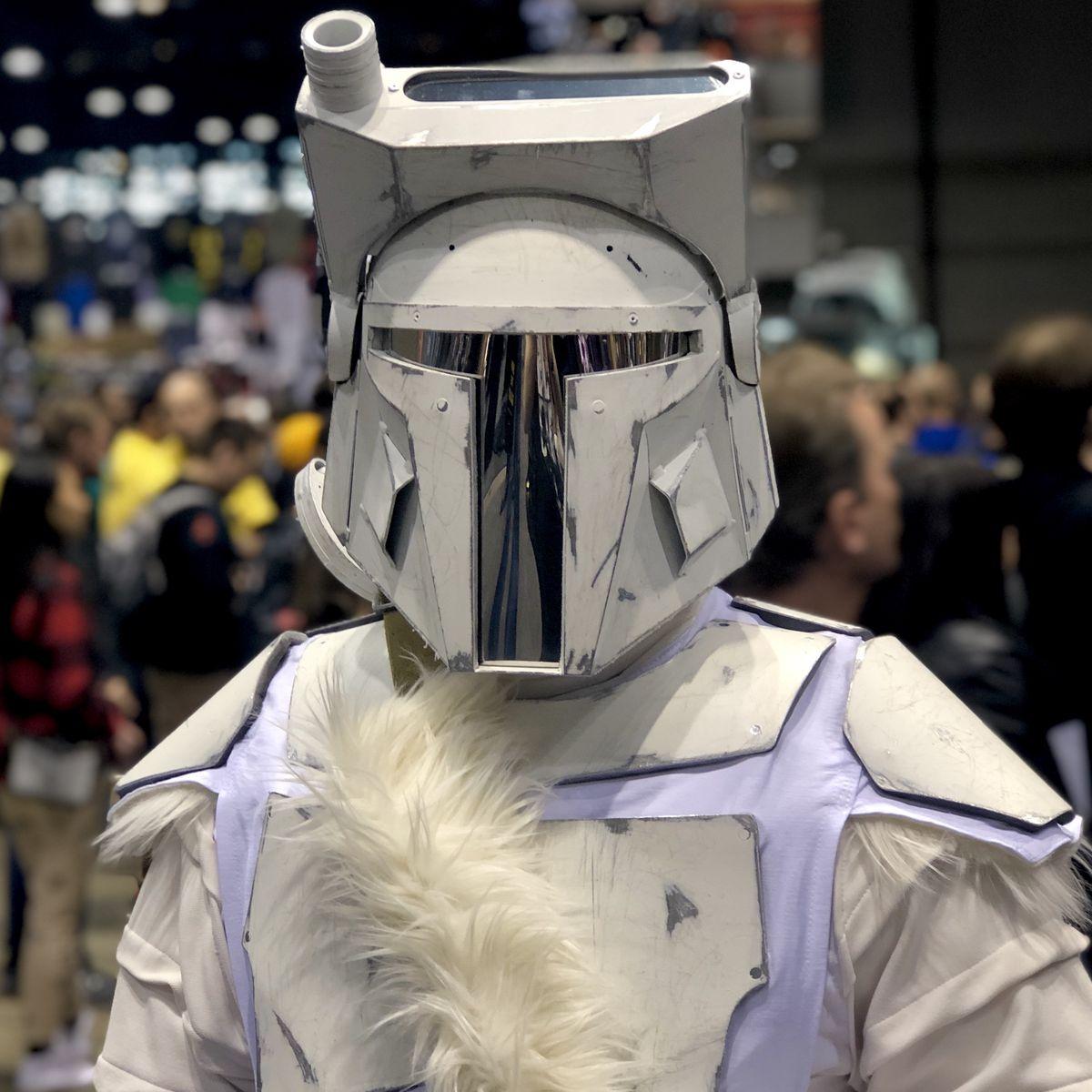 a furry white snow mandalorian armor cosplayer