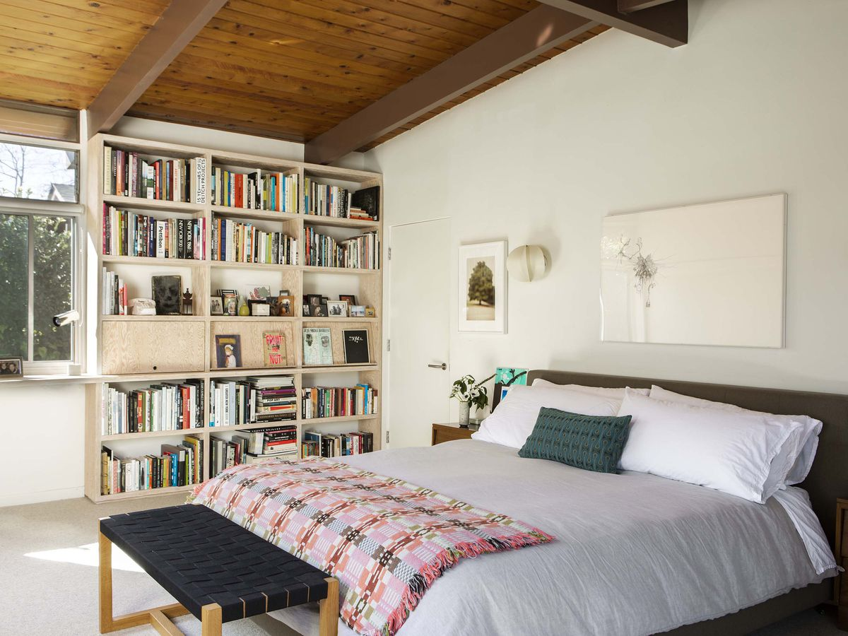 A bed has a light wood bookshelf near it filled with books.