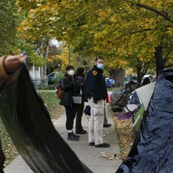Salt Lake detective Joseph Taylor and social worker Karen Montano watch as homeless people pack up their belongings prior to being evicted from Taufer Park in Salt Lake City on Friday, Oct. 23, 2020.