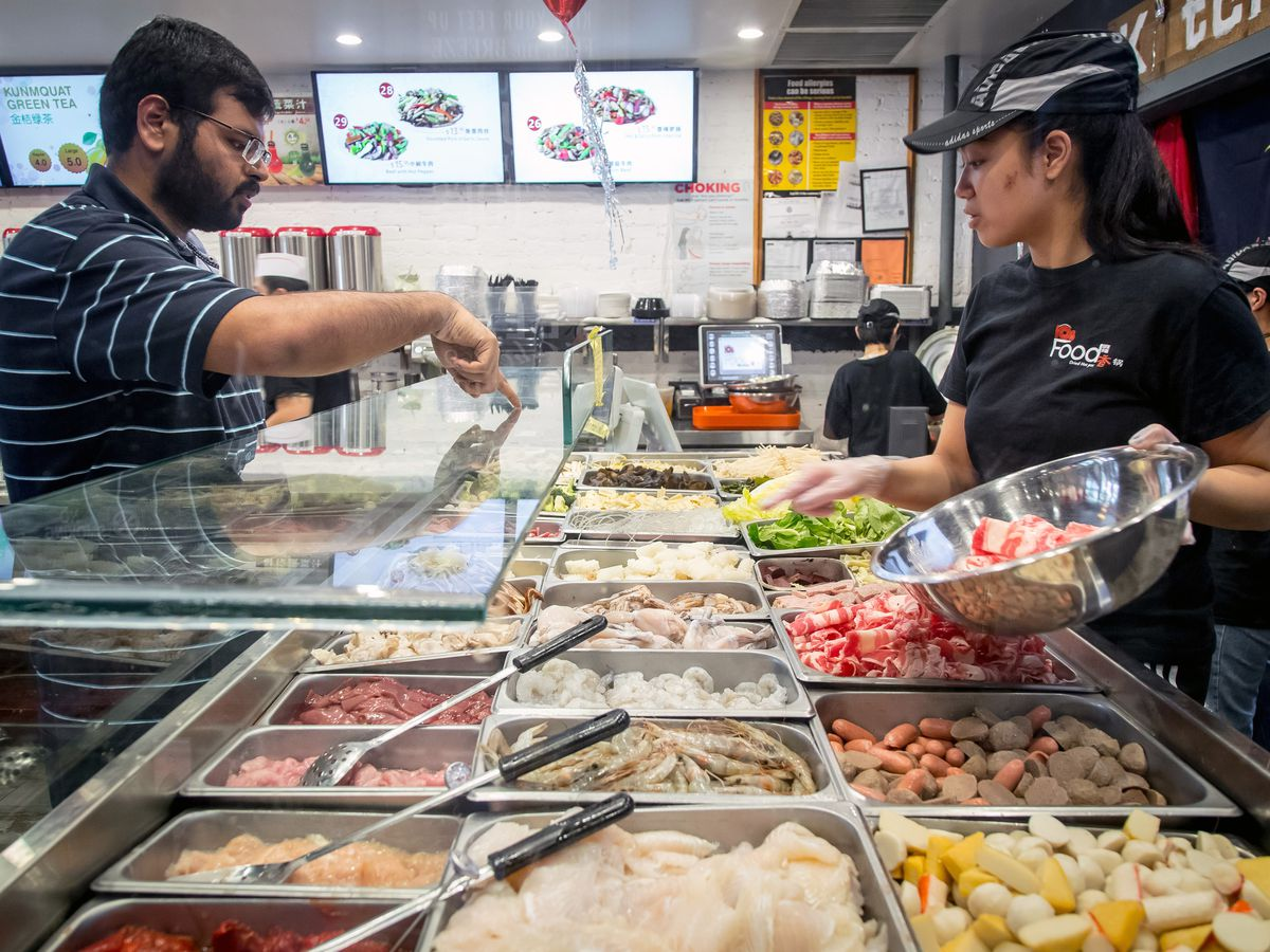 A man pointing at stir-fry ingredients as a worker fills a bowl with his choices