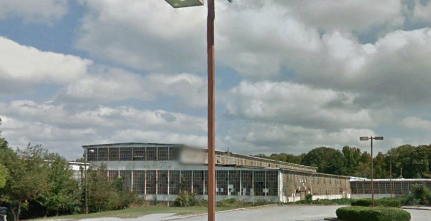 An abandoned arena building with a parking lot in front of it.