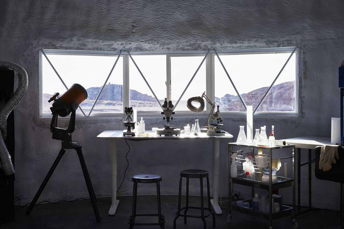 Stools at desk filled with science instruments. A horizontal window looks out to desert landscape. A stainless steel cart on wheels holds lab beakers.