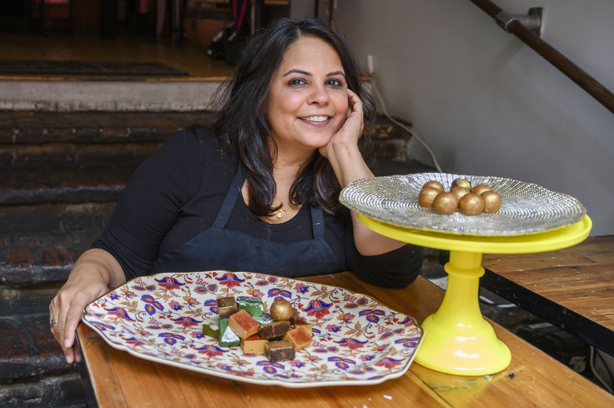A chef with long dark hair, a black shirt, and a dark blue apron sits smiling behind two platters of colorful desserts.