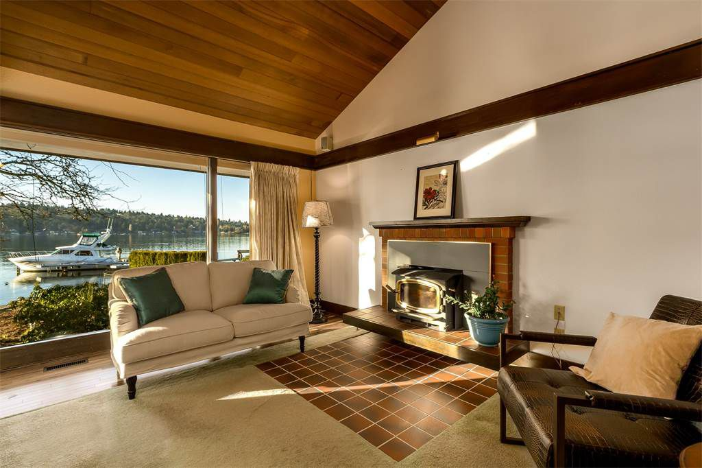 A couch and a chair bookend a fireplace. Large window shows lake and boat.