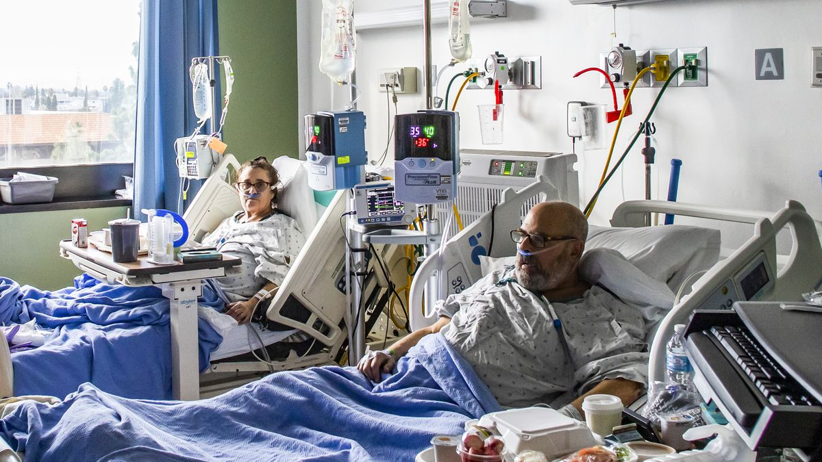 Two patients sitting up in hospital beds.