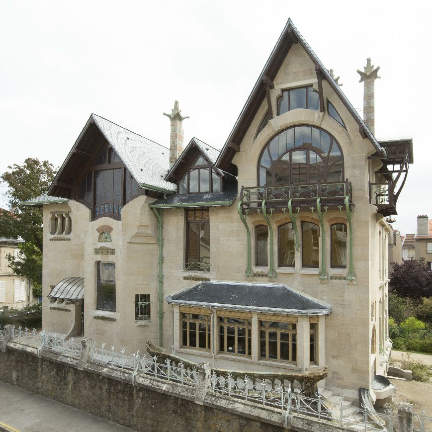 Exterior of stately stone home with curves and intricate details.