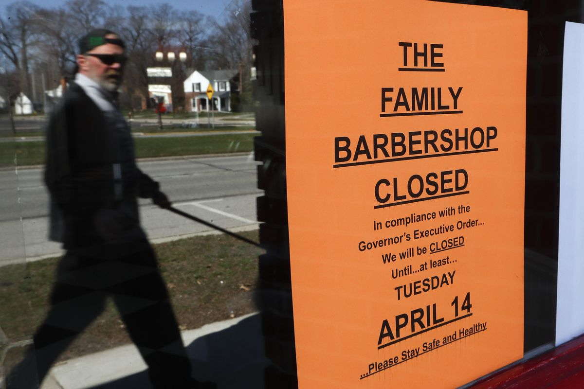 A pedestrian walks by The Family Barbershop, closed due to a Gov. Gretchen Whitmer executive order, in Grosse Pointe Woods, Mich.,