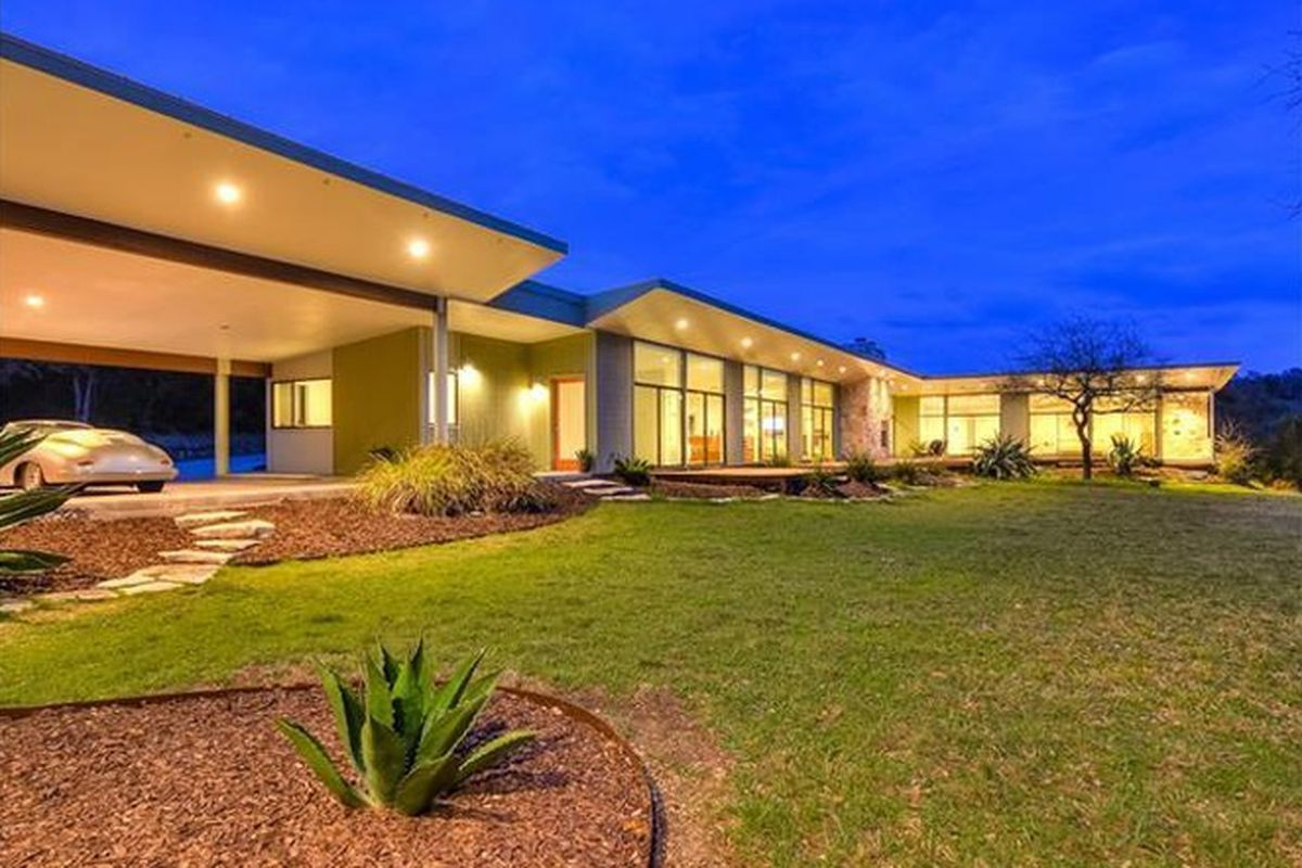 large modern-style home, low profile, lots of windows, slightly sloped roof, aglow with light inside, sunset
