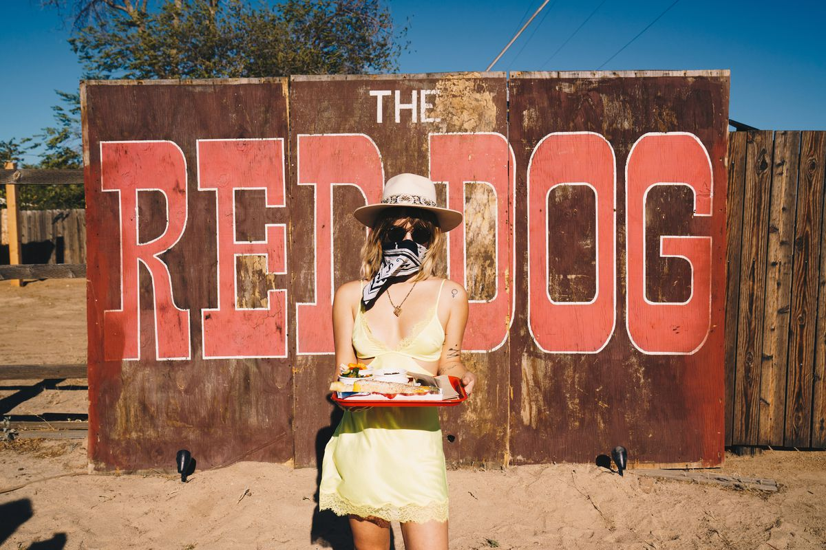 A woman in a yellow sun dress shows off a platter of food next to a large wooden sign.