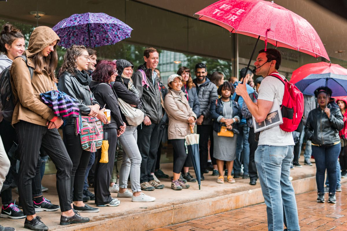A man holding an umbrella stands in front of a large group of people assembled on the sidewalk.
