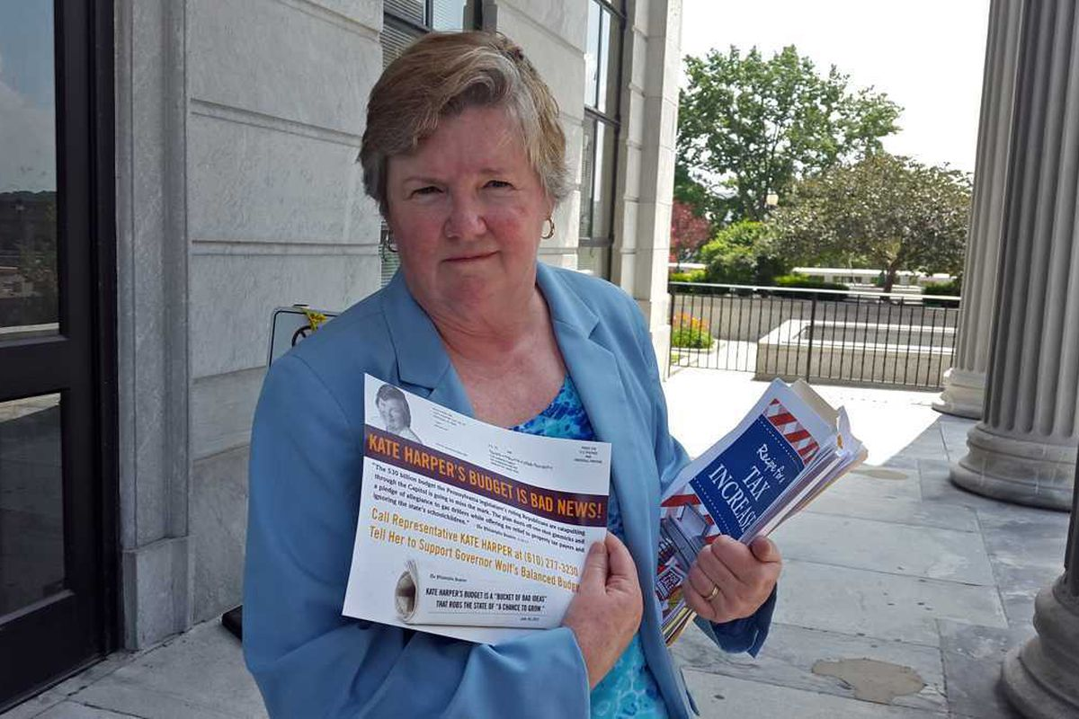 Representative Kate Harper holding a flyer.
