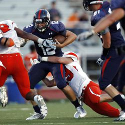 Woods Cross #12 Skyler Farnes, center, is tackled by Mountain Crest's #19 Nick Taylor during play Friday, Aug. 31, 2012.