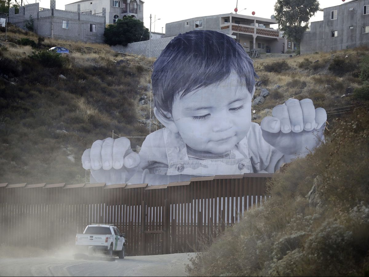A Border Patrol vehicle drives in front of a mural in Tecate, Mexico, just beyond a border structure Friday in Tecate, Calif. A French artist aiming to prompt discussions about immigration erected a 65-foot-tall cut-out photo of a Mexican boy, pasting it