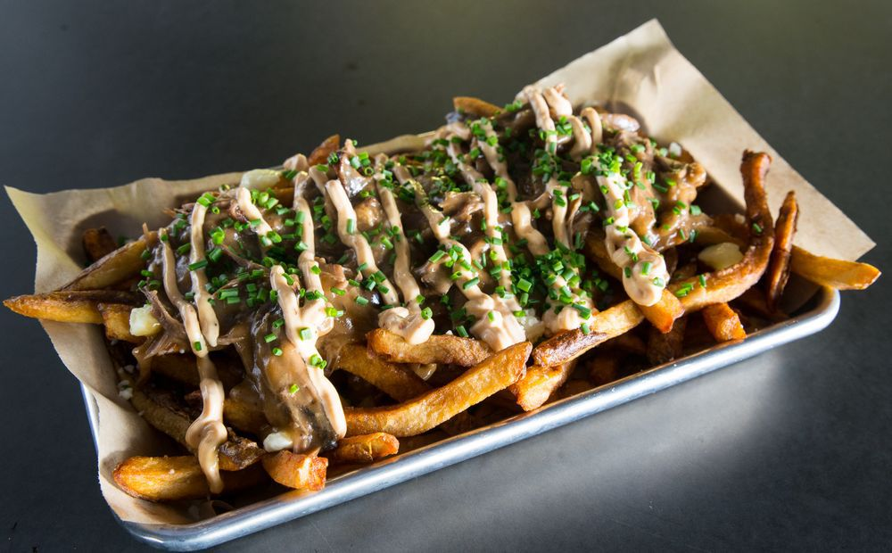 A plate of poutine, with cheese, gravy, mayo, and brisket