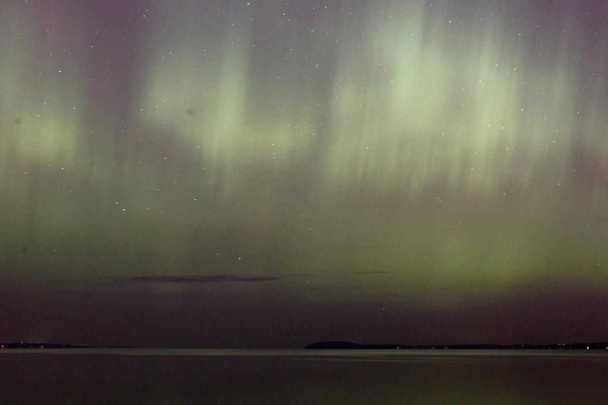 The northern lights shine over West Grand Traverse Bay near Traverse City, Mich., on Monday night, Oct. 24 2011. The lights, also known as aurora borealis in the northern hemisphere, are caused by charged particles striking the Earth's atmostphere.