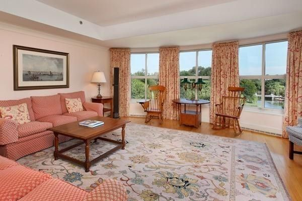 A spacious living room with furniture and three windows overlooking a park.
