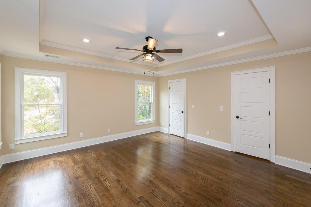 Empty bedroom with tray ceiling, two windows, and two doors.