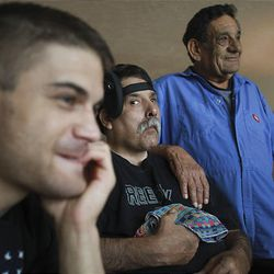 Radly Martinez, left, his father, Richard, and his grandfather Alberto watch TV at their home in West Jordan. Richard suffered brain damage in a 1991 automobile accident.