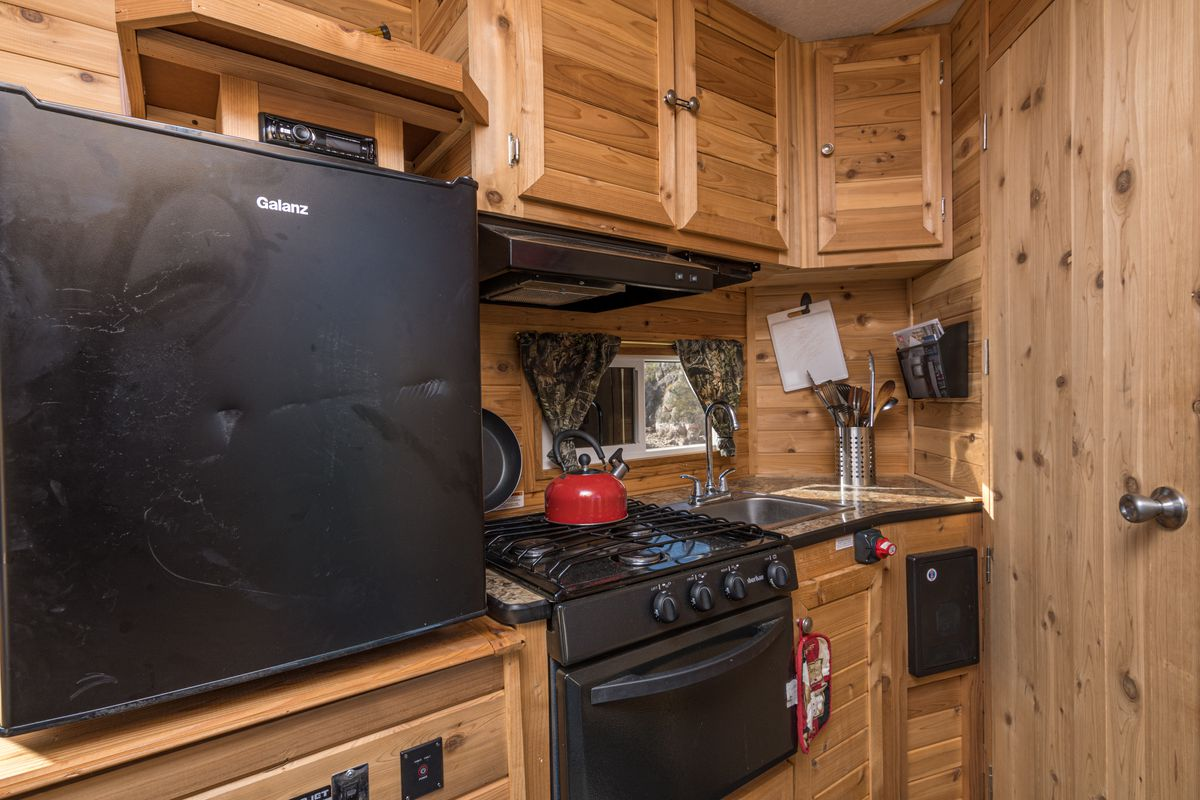 A kitchen galley area includes a black fridge, stove top and oven, wood-paneled walls, and wooden cabinets.