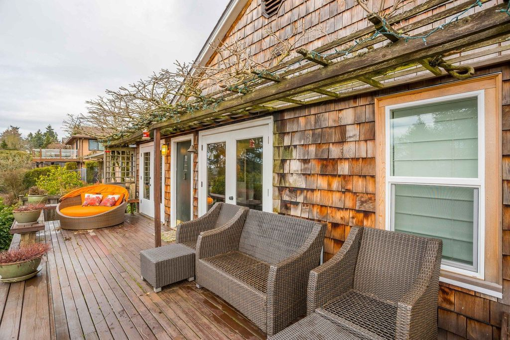 A wood shingled house with a trellis, shot fro the large front deck
