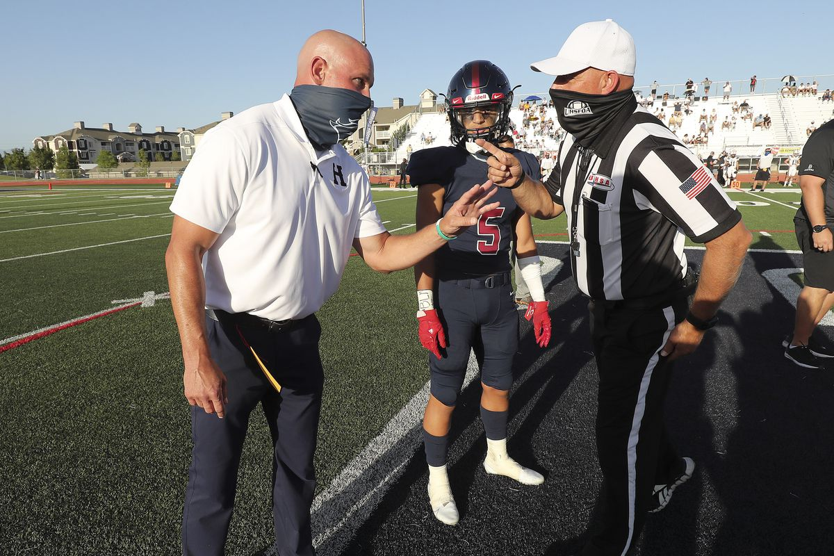 Herriman head coach Dustin Pearce has trouble hearing the referee as they wear masks after the coin toss as Herriman plays Davis in Herriman on Thursday, Aug. 13, 2020. The game is the first high school football game since the pandemic began.